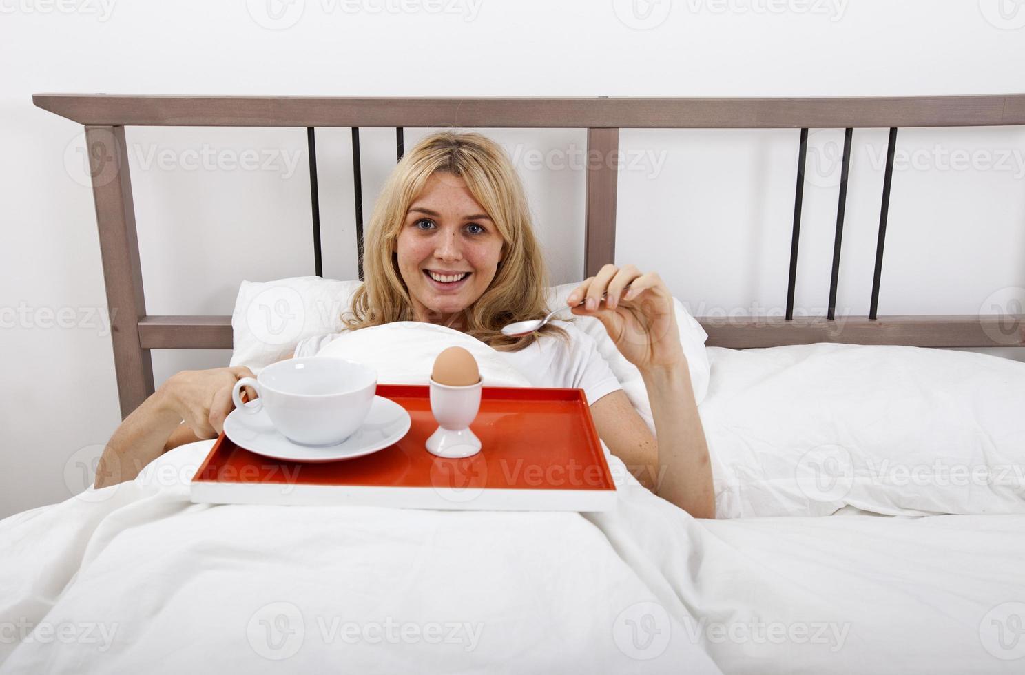 Porträt der jungen Frau mit Frühstückstablett im Bett foto