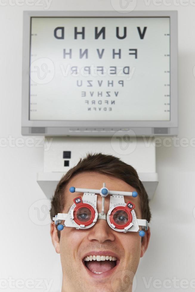 glücklicher Mann am Optiker, der Sehtest hat foto