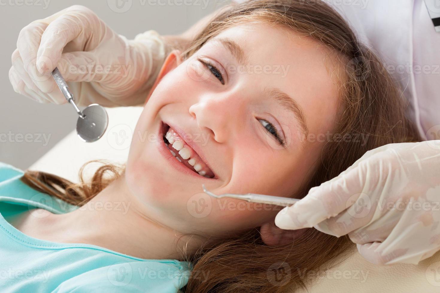 glückliches Mädchen, das Zahnbehandlung unterzieht foto