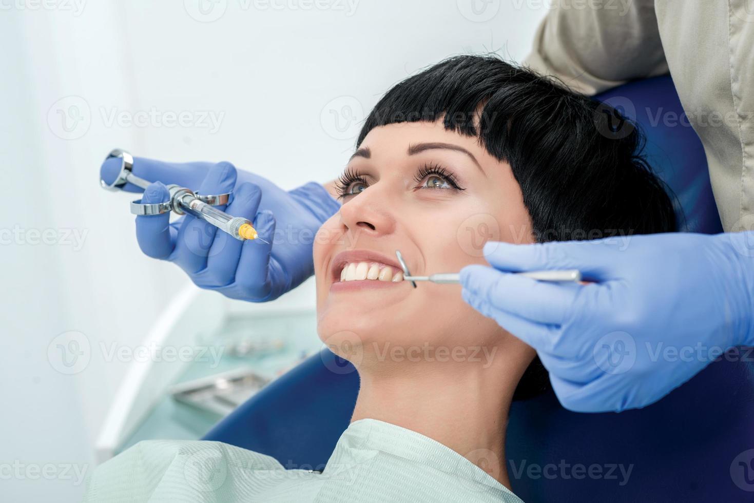Machen Sie glücklichen Kunden die Anästhesie. Zahnarzt macht den Prozess foto