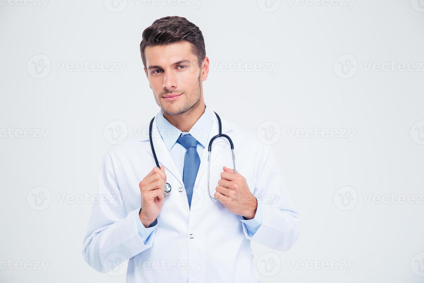Porträt eines männlichen Arztes, der mit Stethoskop steht foto