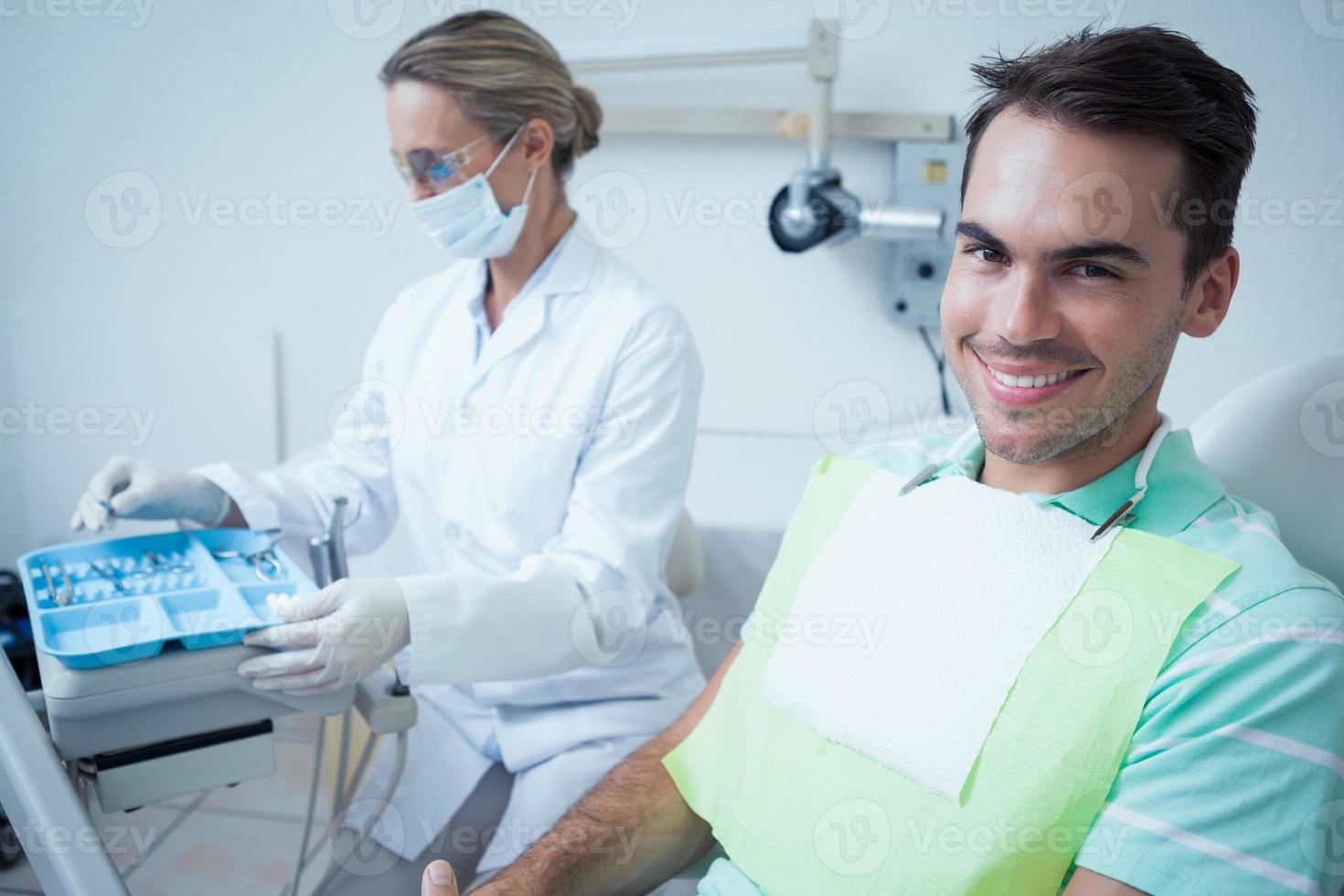 lächelnder Mann, der auf Zahnuntersuchung wartet foto