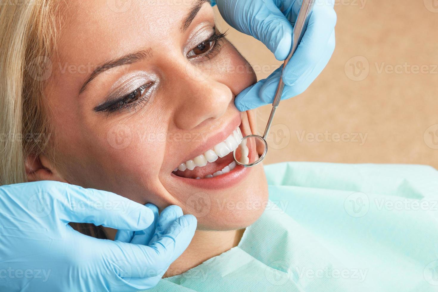 Nahaufnahme der jungen Frau, die ihre Zähne untersucht hat foto