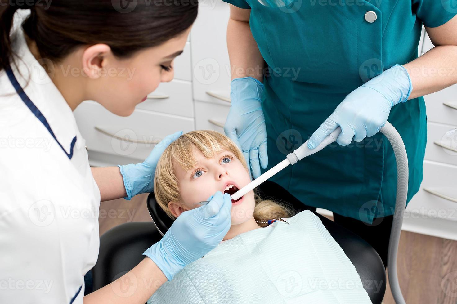 Zahnarzthelferin behandeln ein kleines Mädchen foto