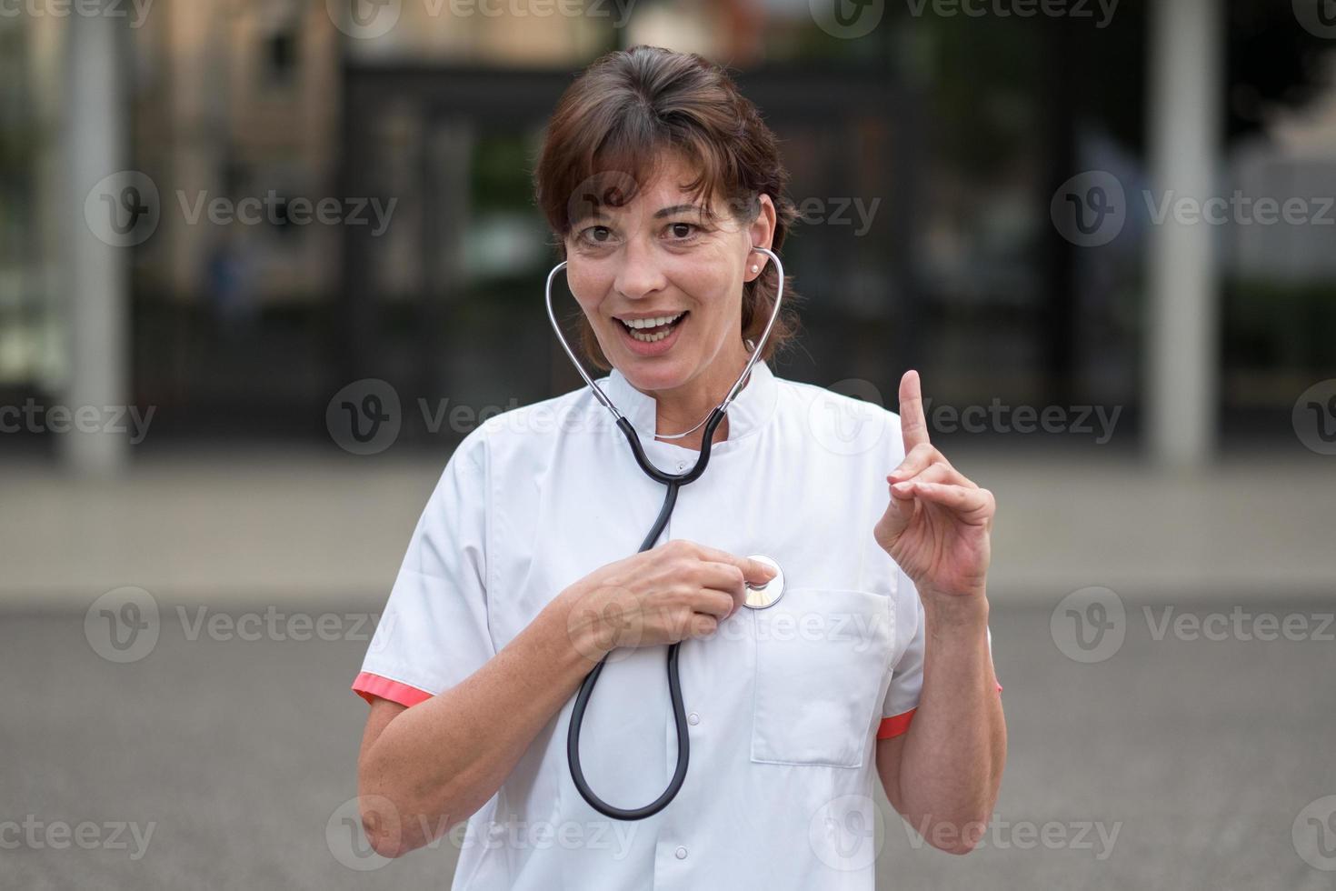 lächelnde Kardiologin, die auf ihr Herz hört foto