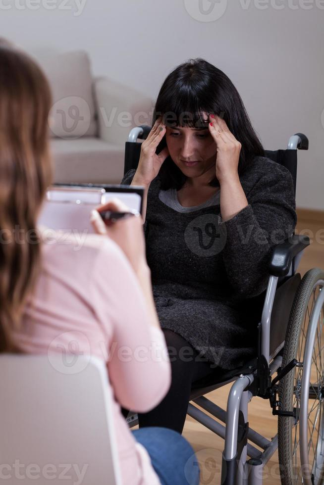 Frau im Rollstuhl im Gespräch mit Therapeutin foto