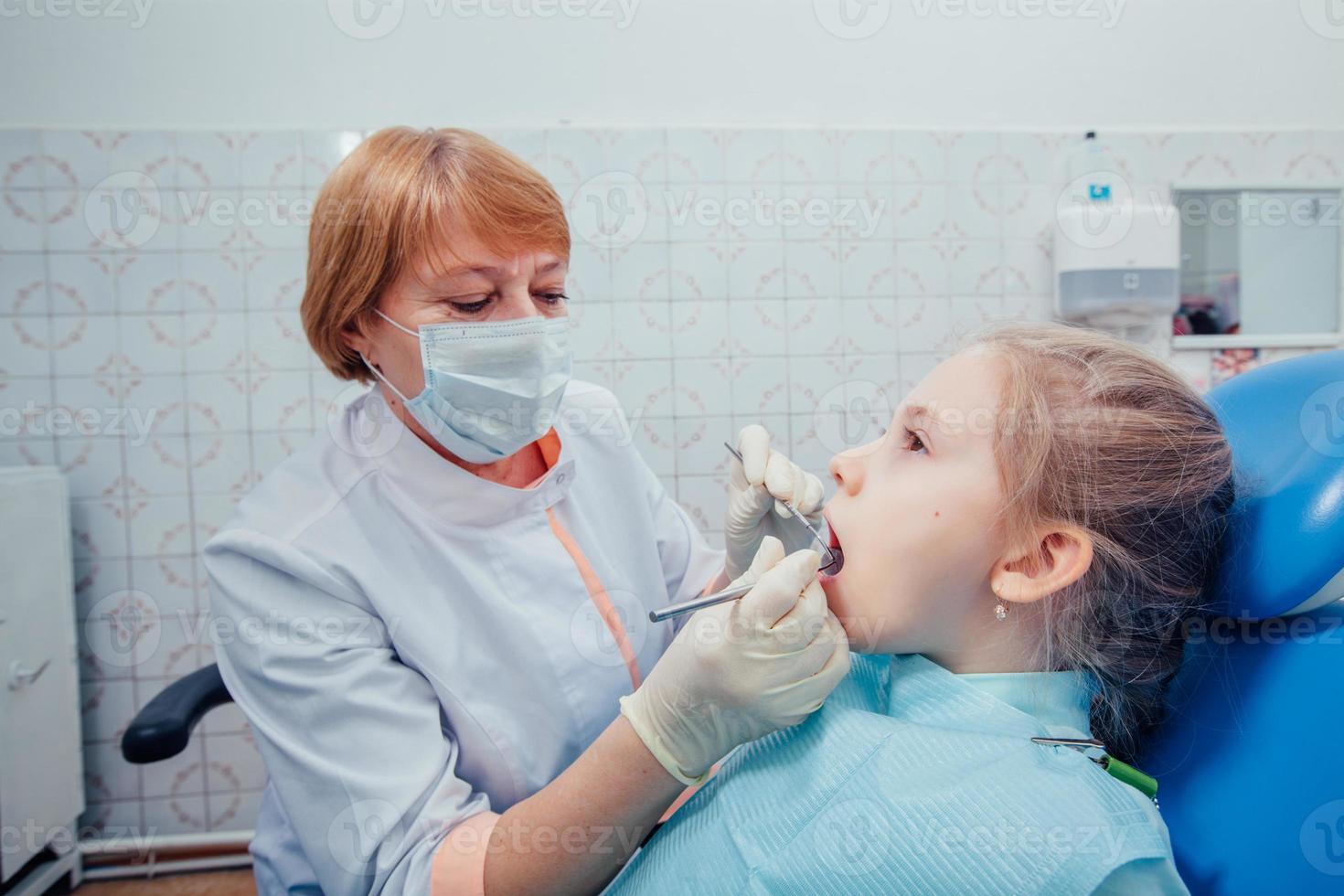 kleines Mädchen sitzt in der Zahnarztpraxis foto