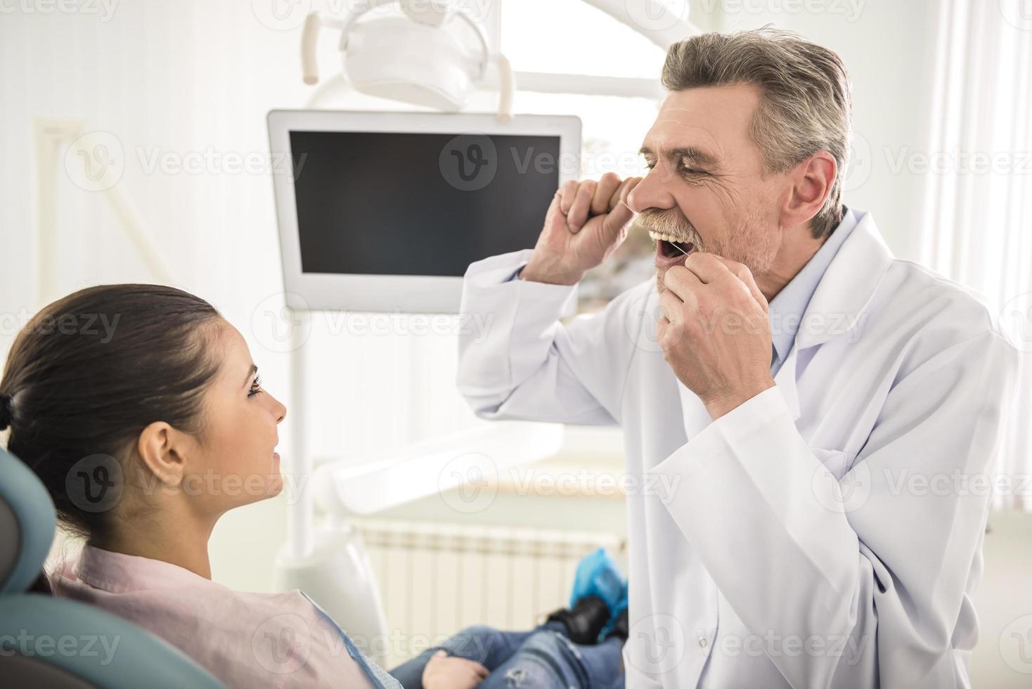 Lehren, wie man Zähne mit Zahnseide richtig putzt. foto