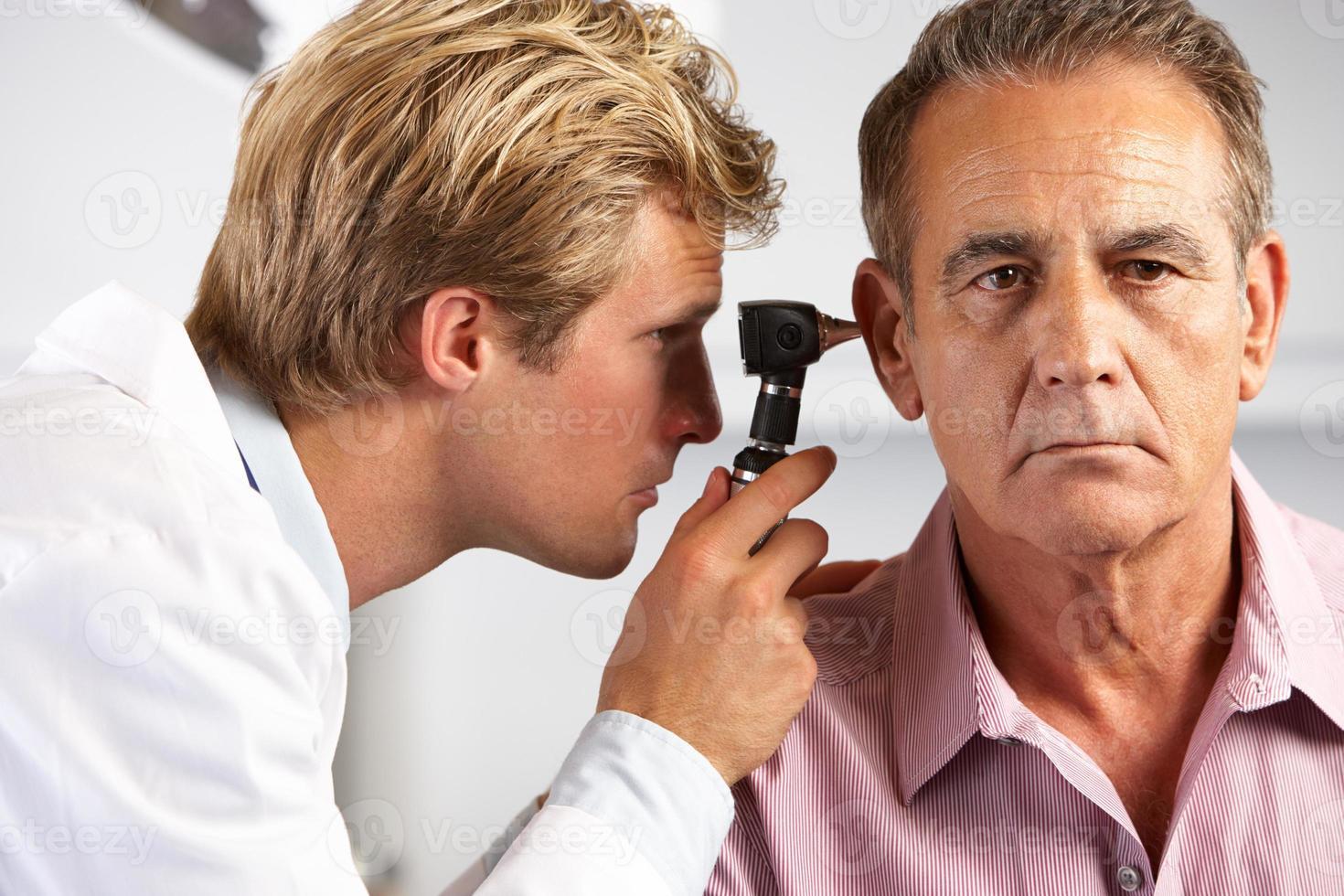 Arzt untersucht die Ohren des männlichen Patienten foto