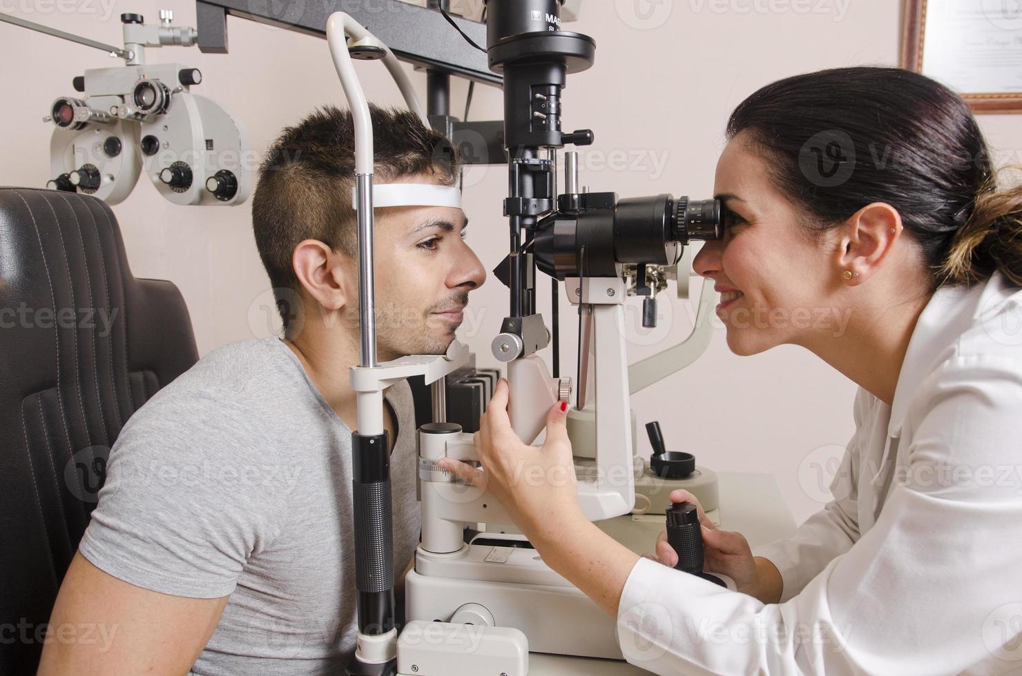 optische Prüfung für jungen Mann, professionelle Frau foto