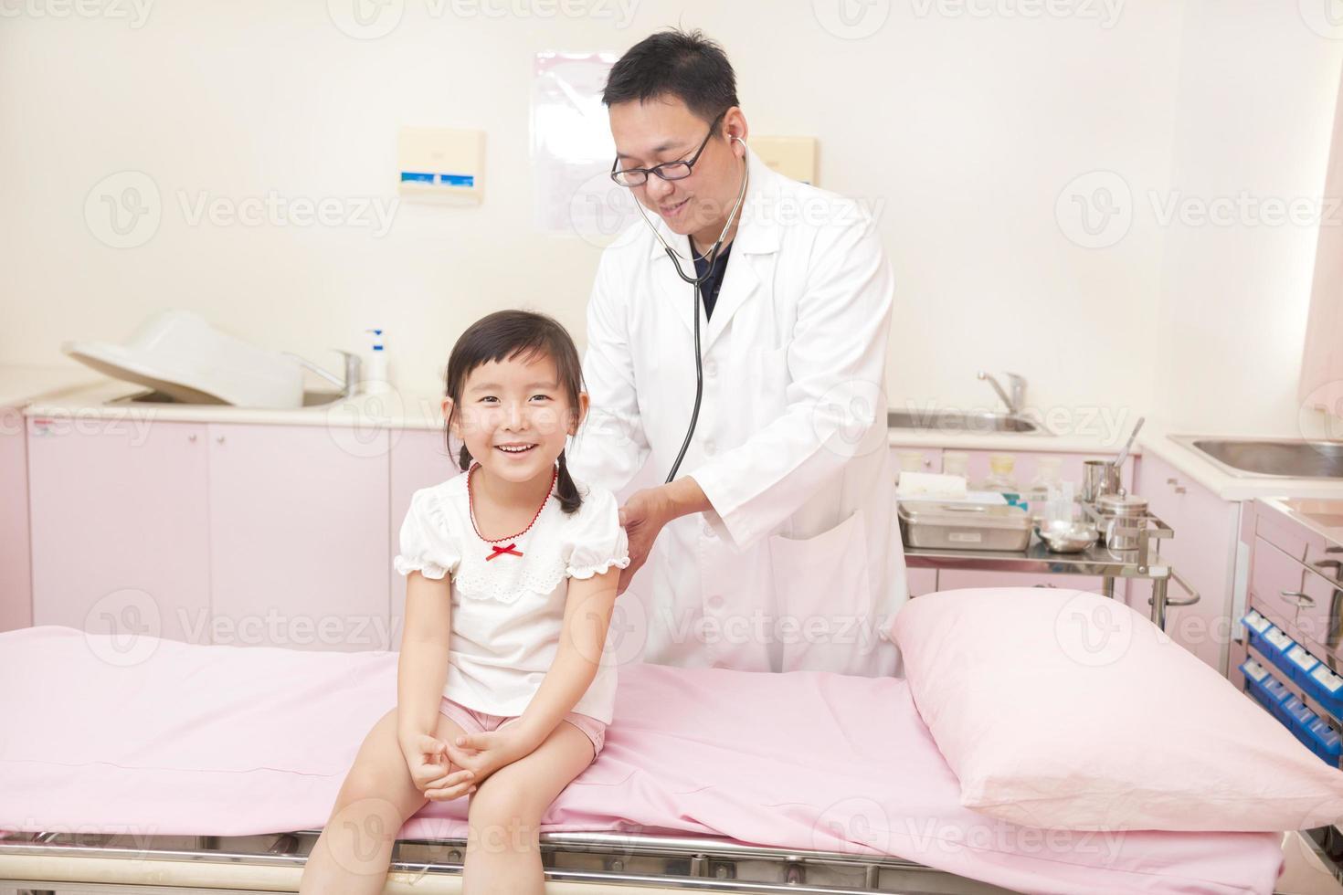 männlicher Kinderarzt, der kleines Mädchen untersucht foto