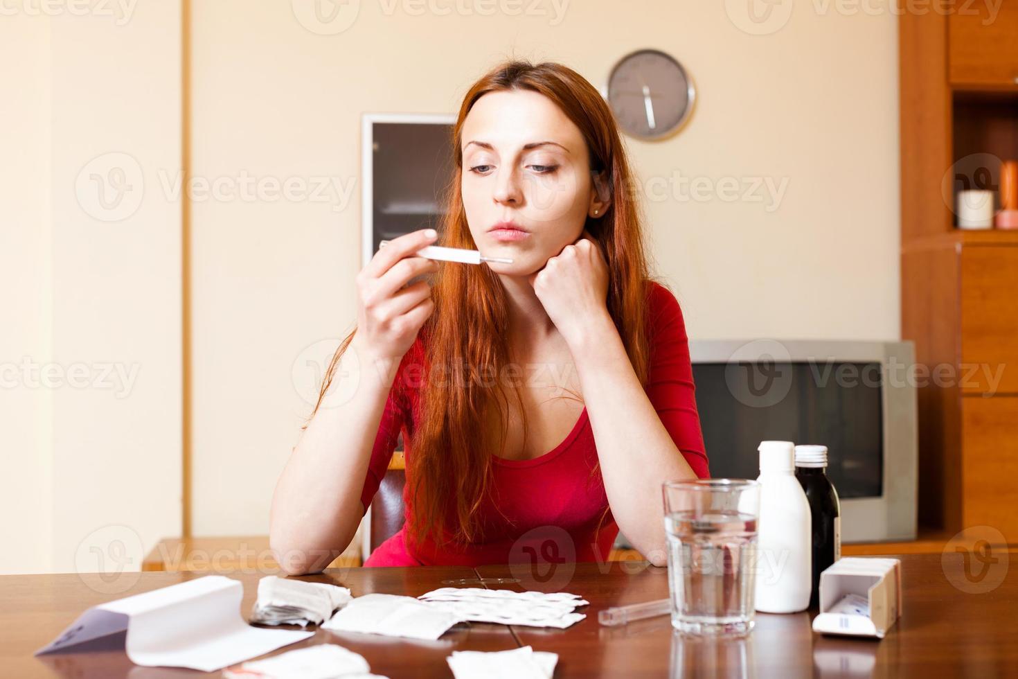 traurige Frau, die Temperatur mit Thermometer zu Hause misst foto