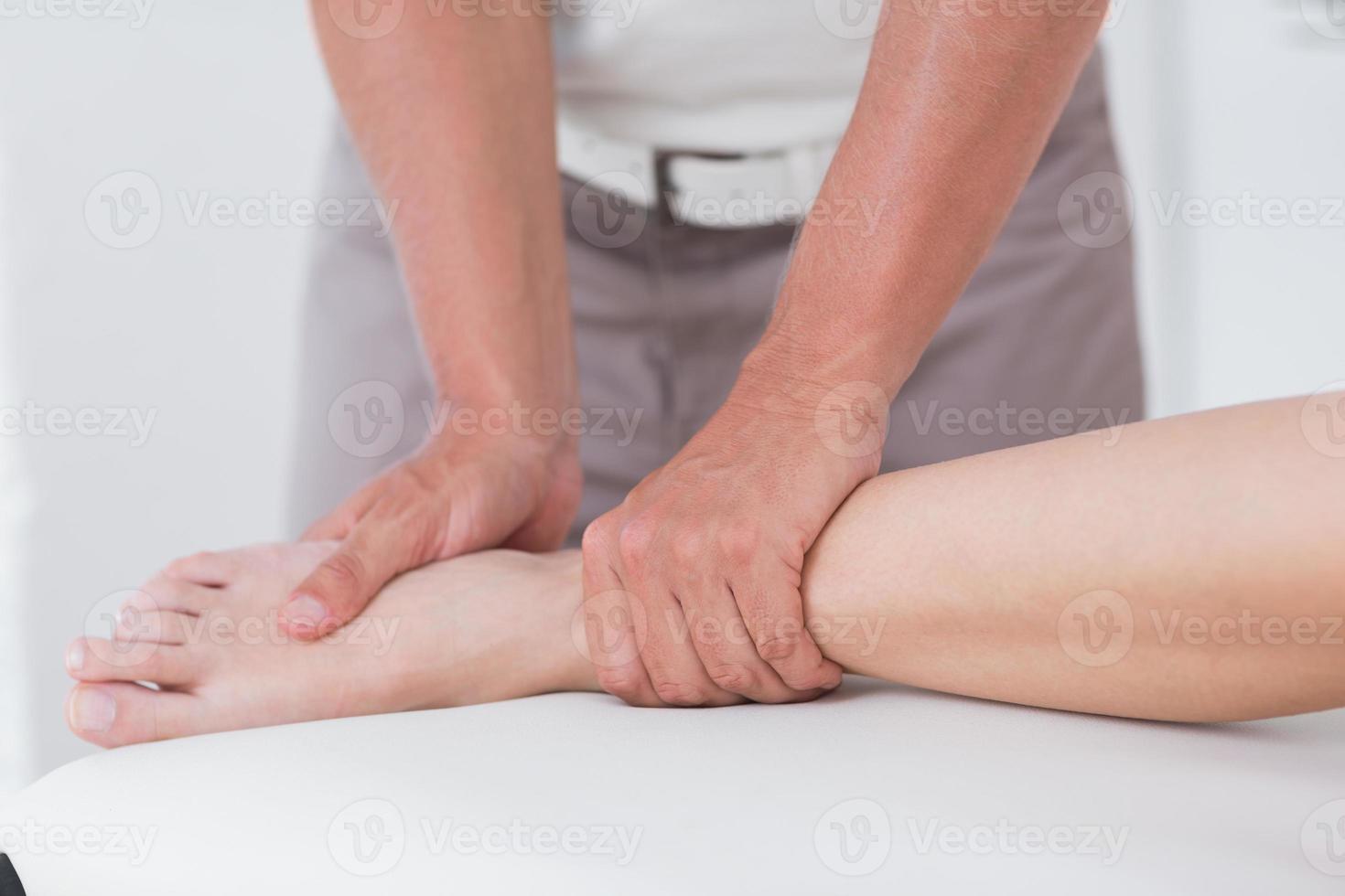 Physiotherapeut bei der Wadenmassage foto