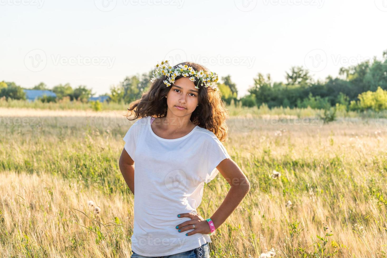 jugendlich Mädchen mit einem Kranz von Gänseblümchen im Feld foto