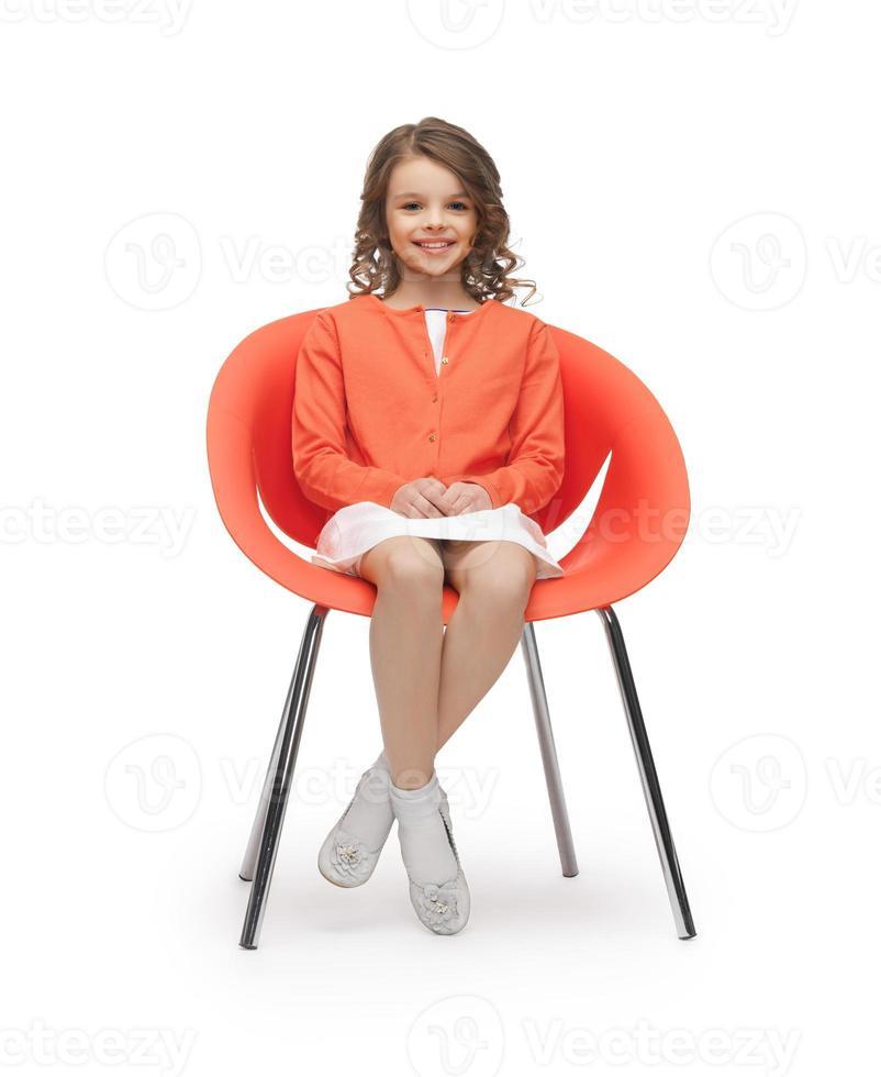 jugendliches Mädchen in der Freizeitkleidung, die auf Stuhl sitzt foto