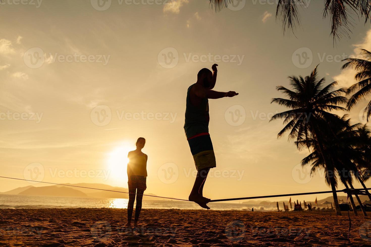 Teenager balancieren auf Slackline-Silhouette foto