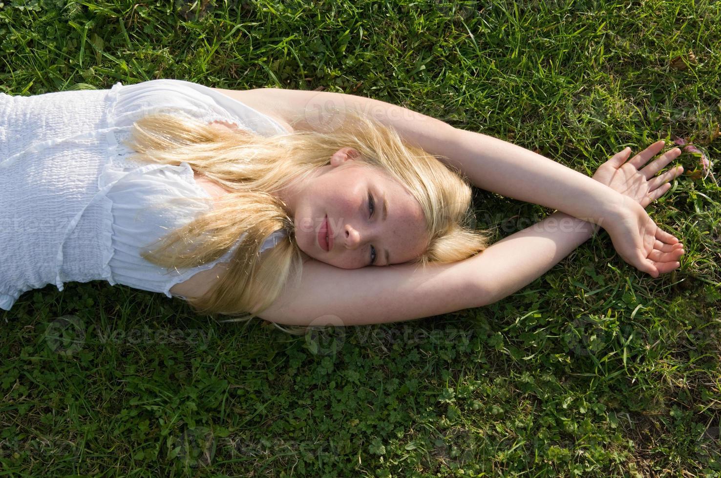 Teenager-Mädchen im Gras liegen foto
