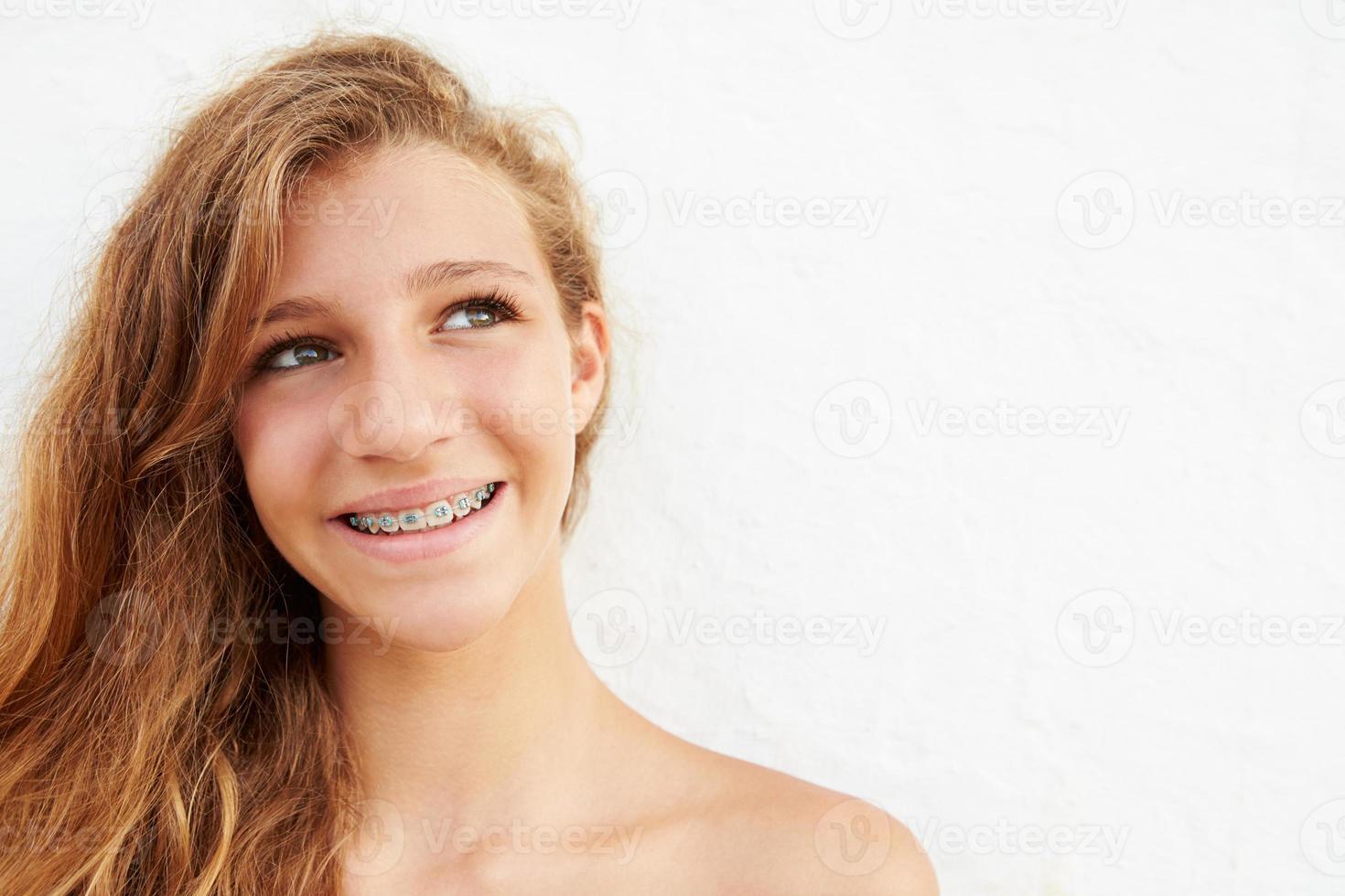 Porträt des Mädchens, das an Wand lehnt foto