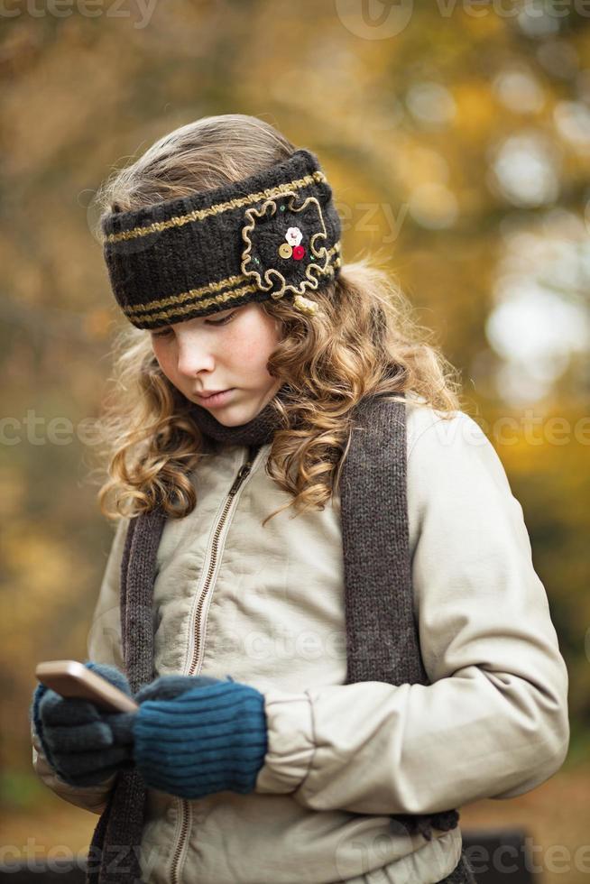 Teenager-Mädchen SMS mit Handy in einem Herbsttag foto