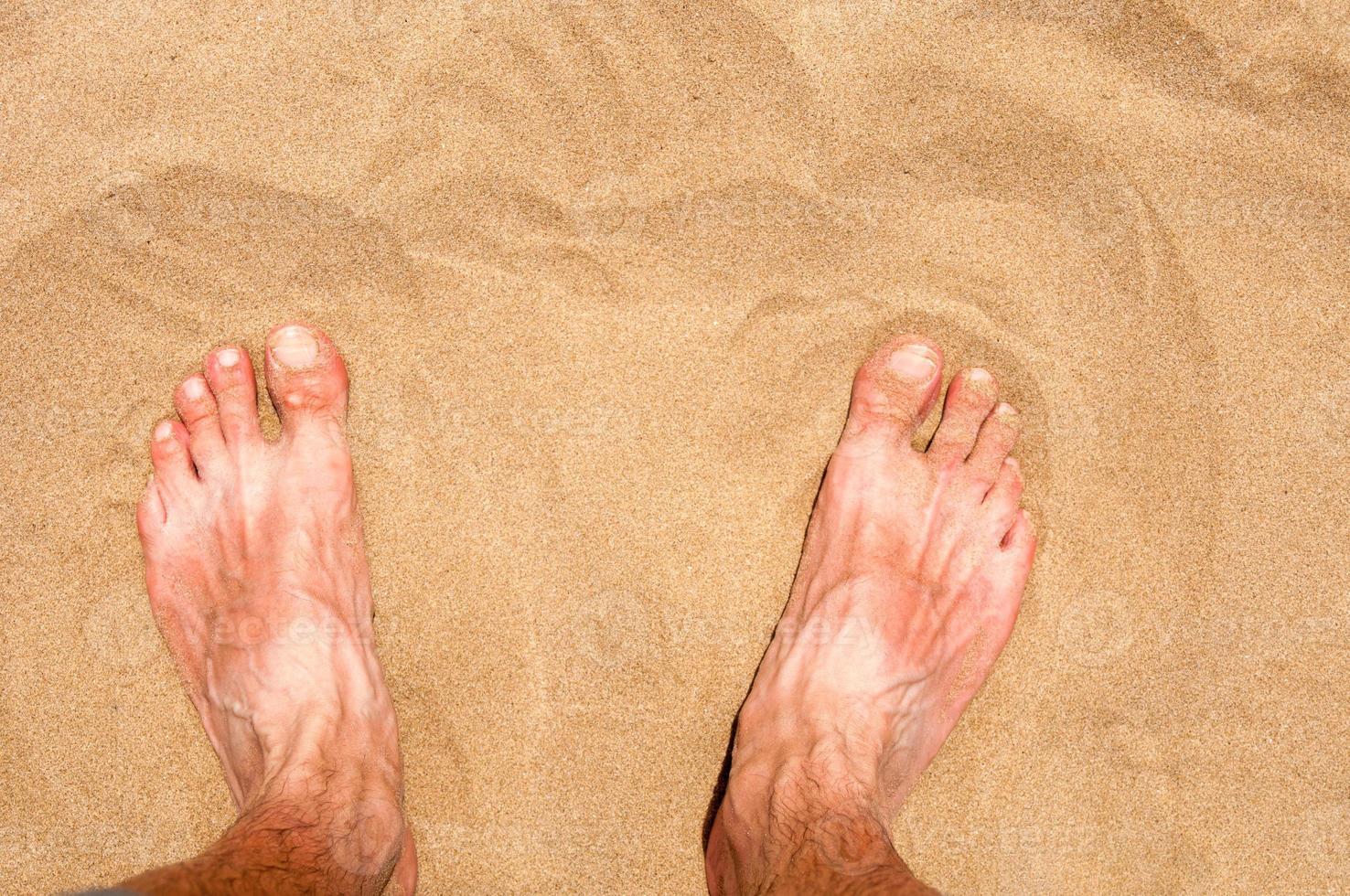 männlicher Fuß auf Sand foto