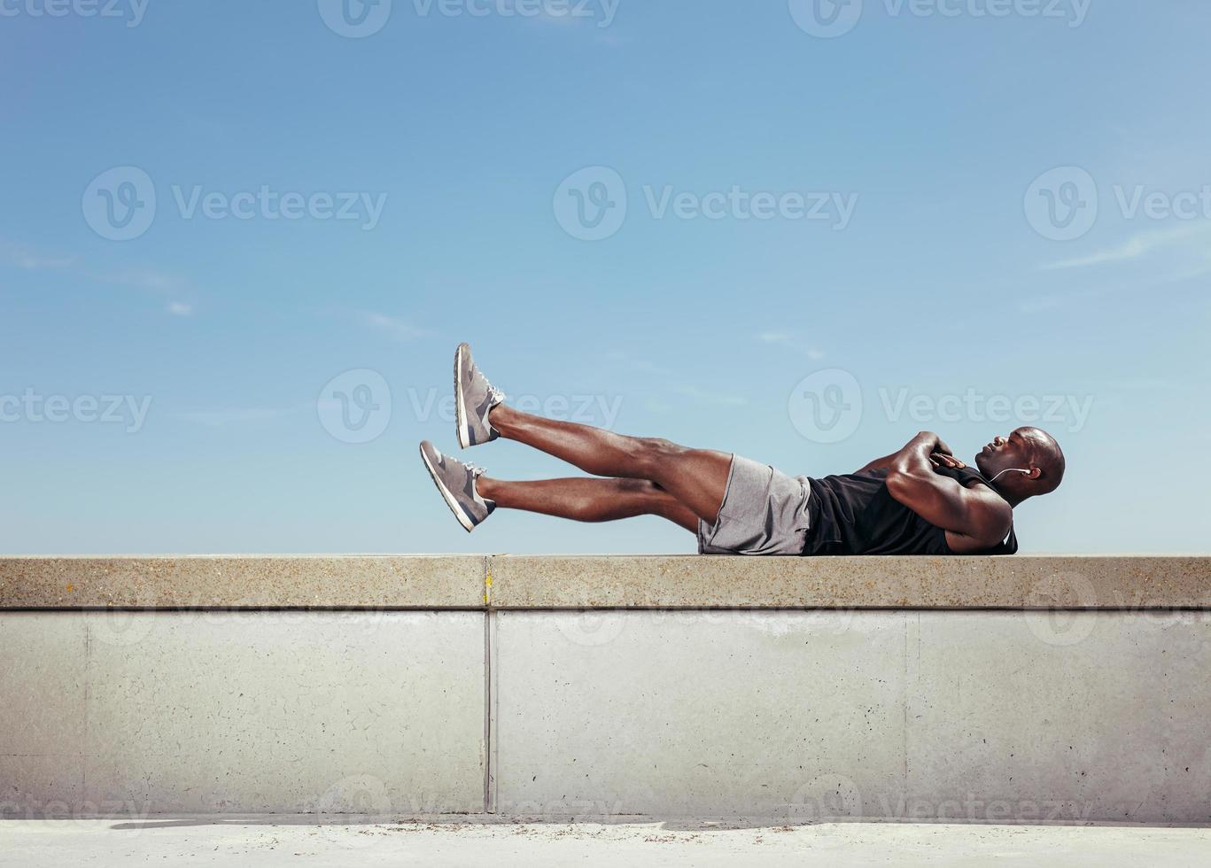 männlicher Athlet, der Bauchmuskeln macht foto