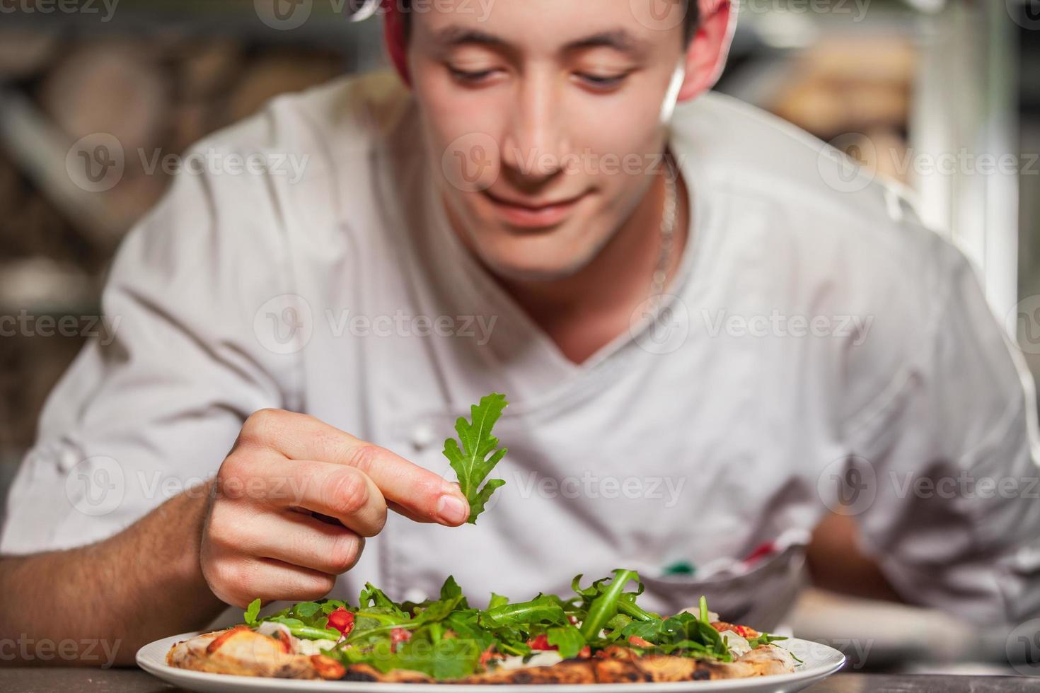männlicher Koch, der köstliche Vorspeise zubereitet foto