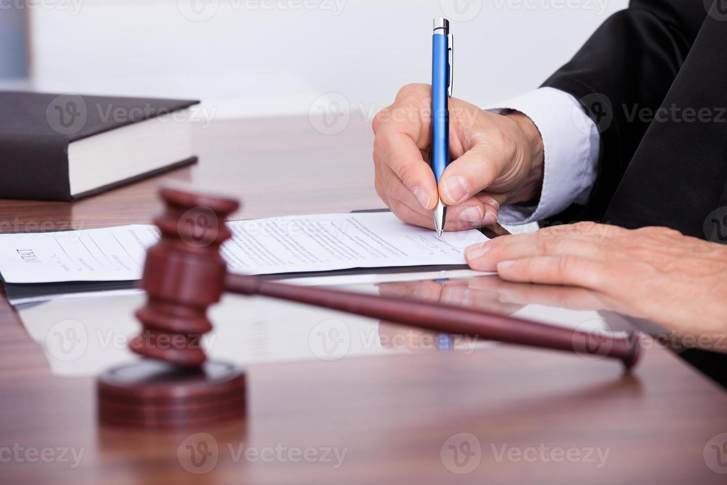 männlicher Richter schreibt auf Papier foto