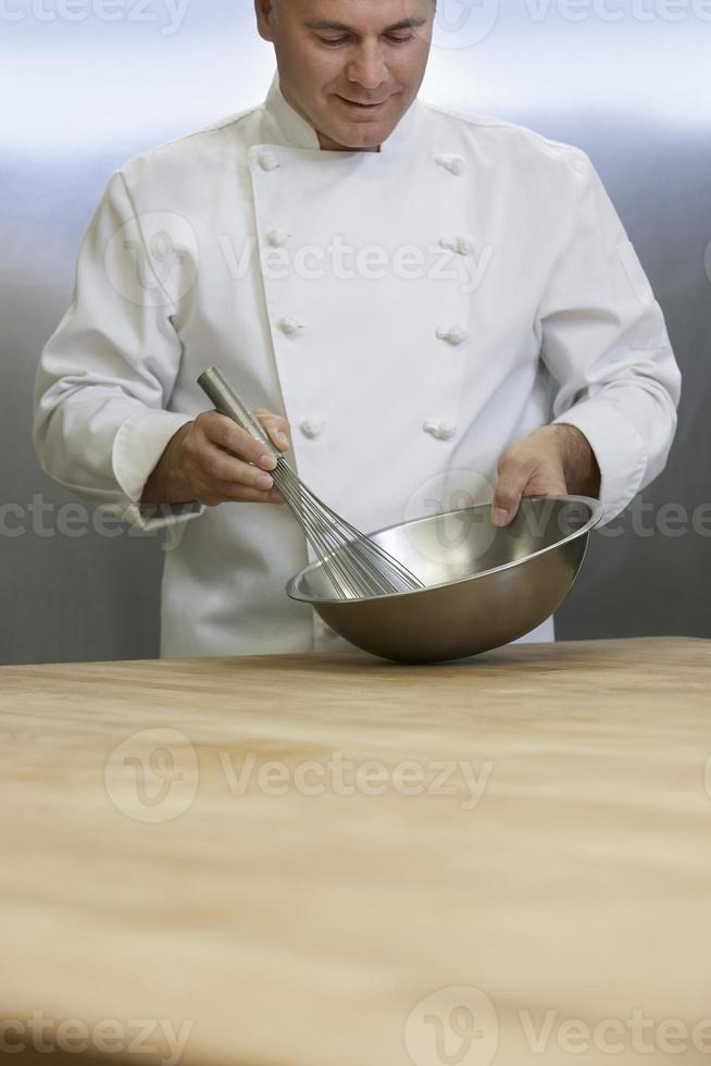 männlicher Koch, der Zutaten mit Schneebesen mischt foto