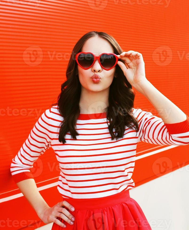Porträt der hübschen Frau in der roten Sonnenbrille, die Lippen bläst foto