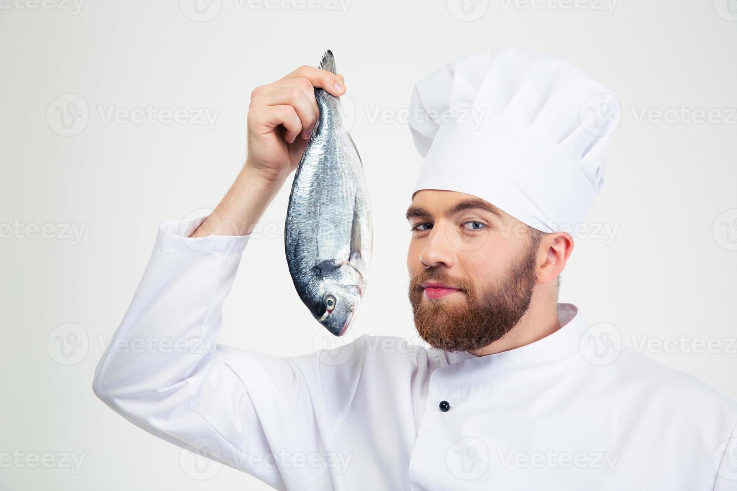 hübscher männlicher Kochkoch, der Fisch hält foto