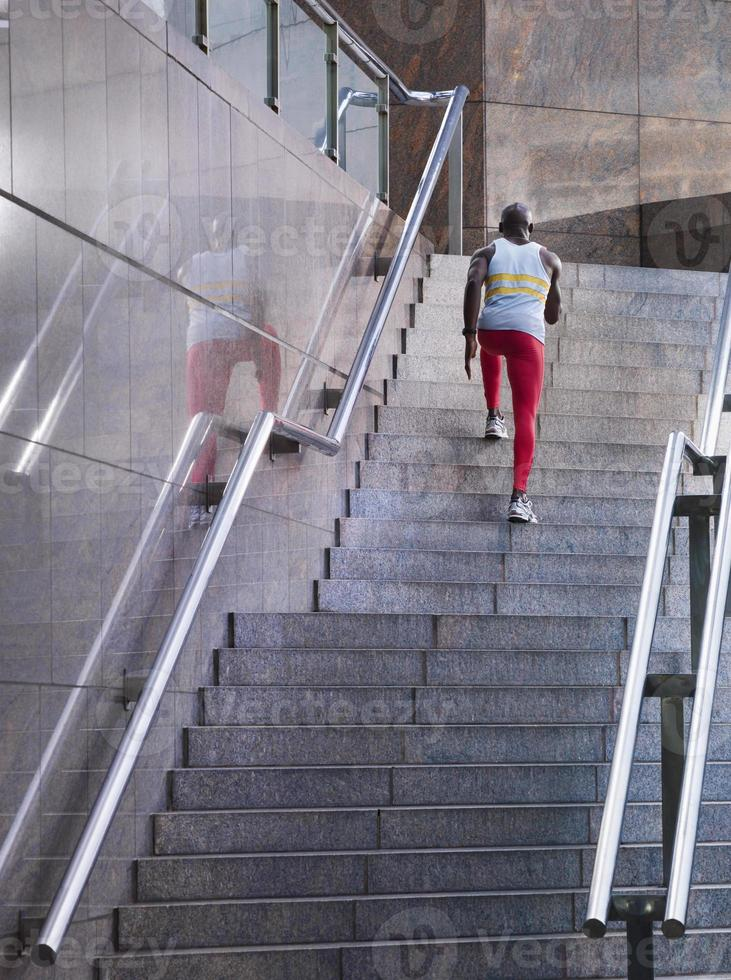 männlicher Athlet, der im Freien die Treppe hinaufläuft foto