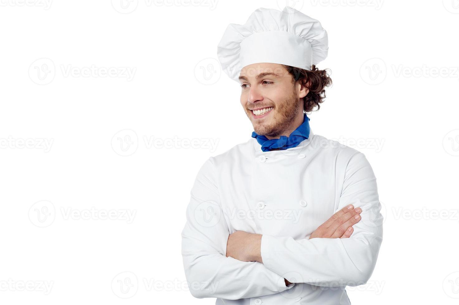 lächelnder junger männlicher Koch, der souverän aufwirft foto