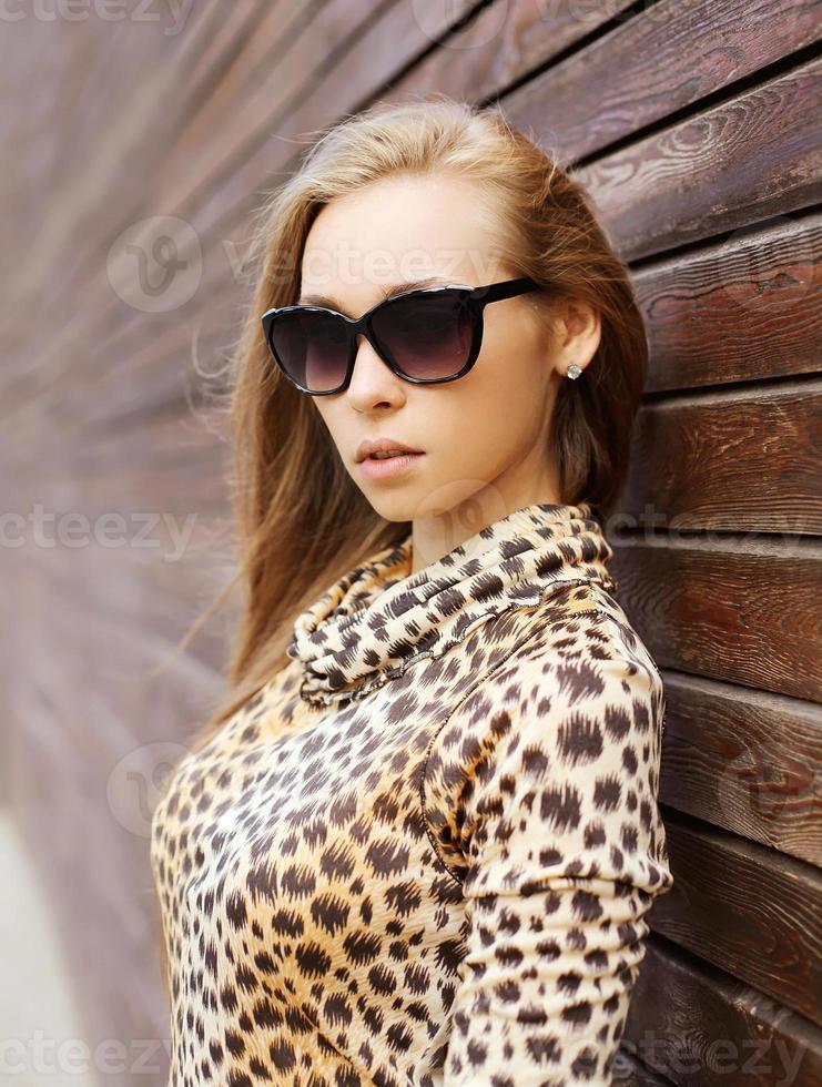 Porträt der schönen jungen Frau, die ein Leopardenkleid trägt foto