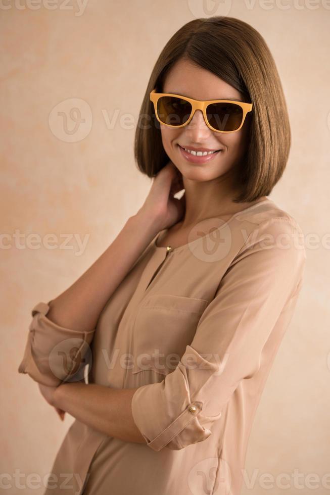Porträt der schönen lächelnden jungen Frau, die Sonnenbrille trägt foto