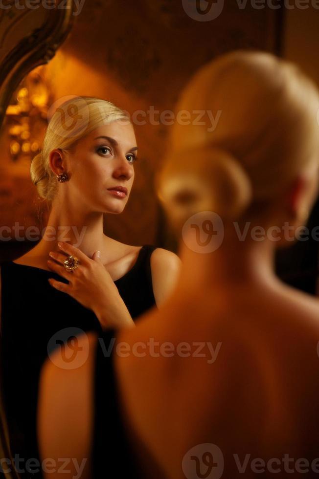 schöne Frau im Weinlesespiegel reflektiert foto