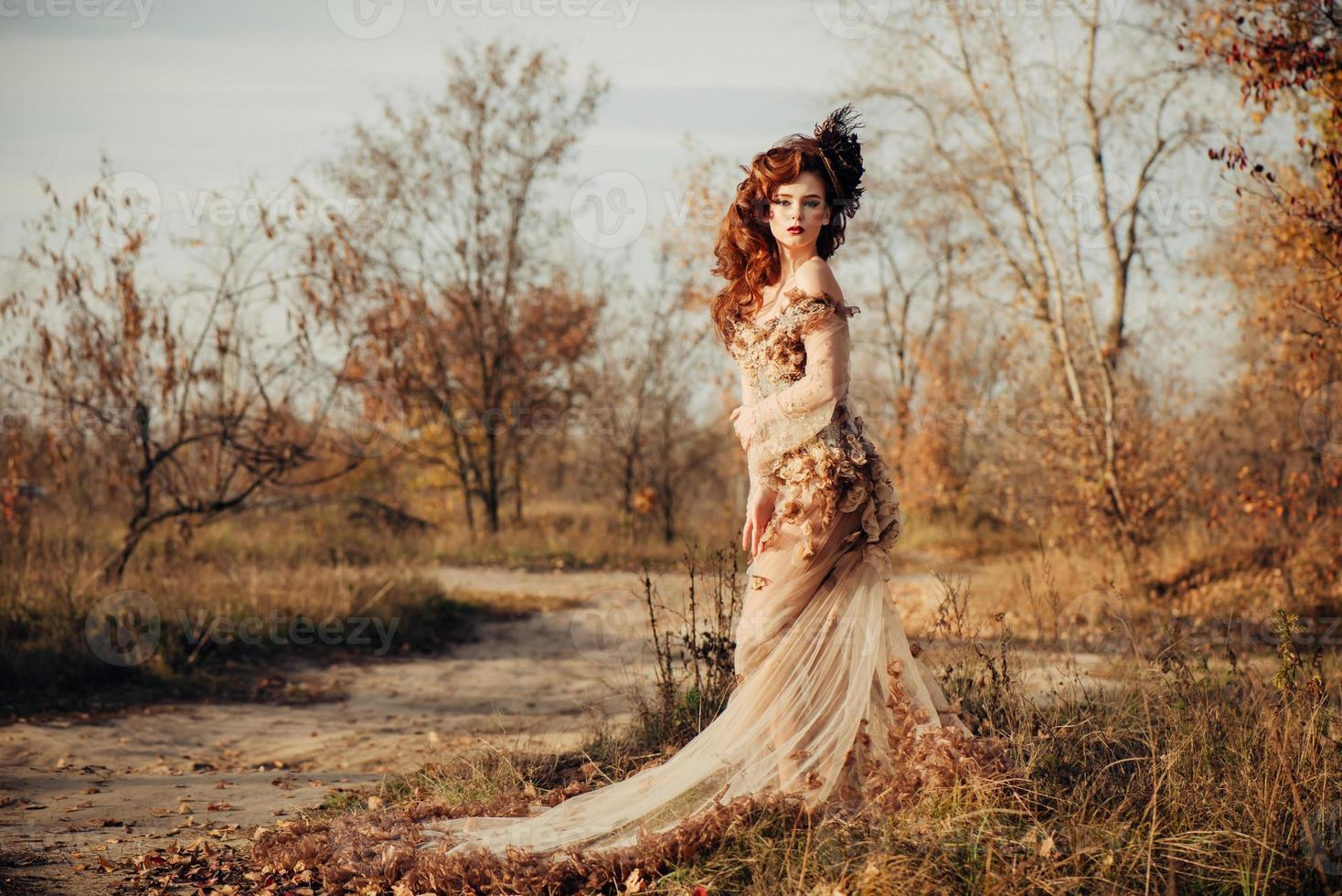 Schönheit Herbstfrau im Kleid mit Blättern foto
