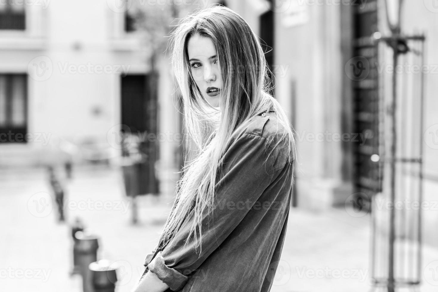städtischer Hintergrund des blonden Mädchens foto