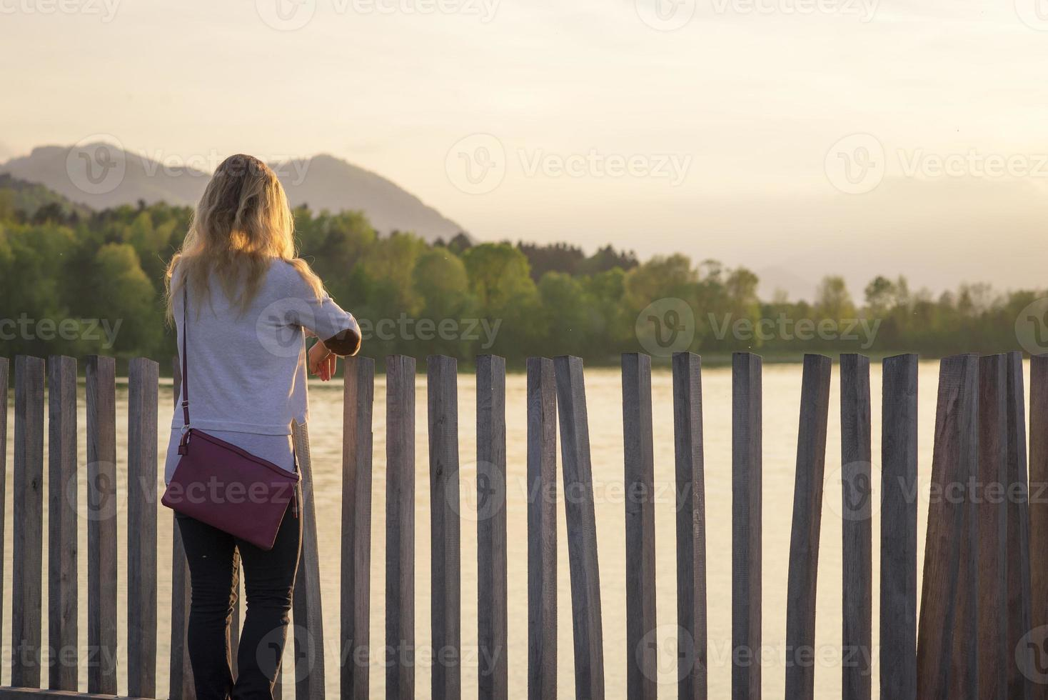 Frau, die Sonnenuntergang am See sucht foto