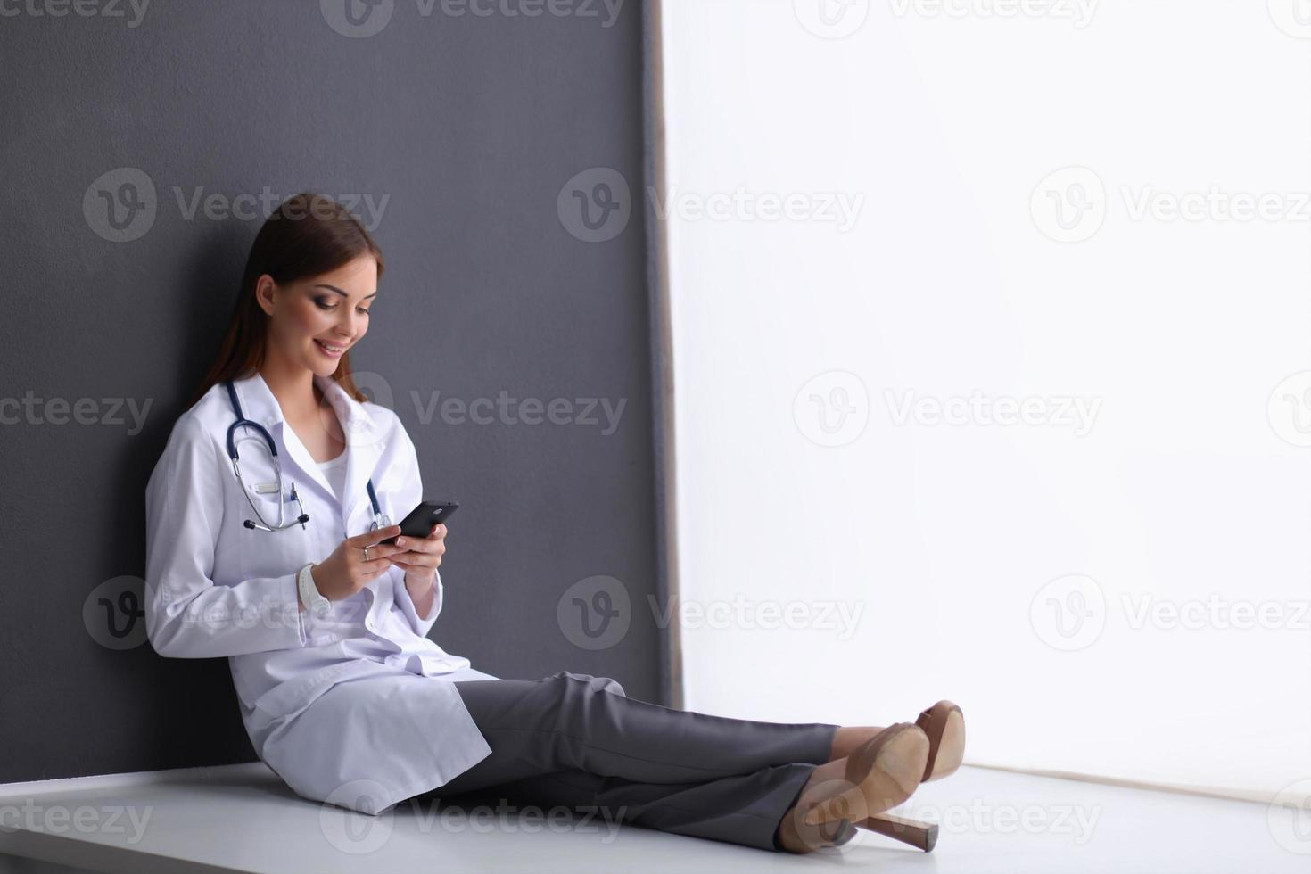 junge Ärztin, die mit Ihrem Telefon auf dem Boden sitzt foto