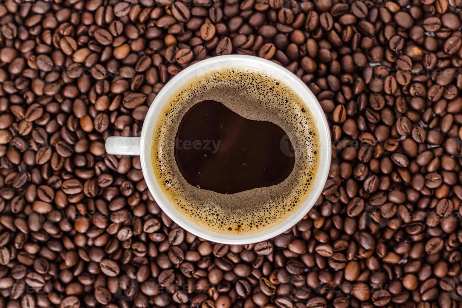 weiße Tasse Kaffee auf einem Haufen Kaffeebohnen. foto