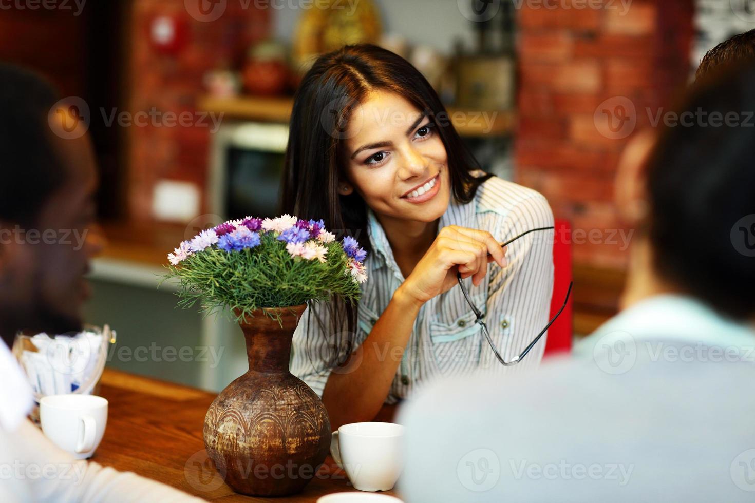Geschäftsfrau mit Brille hört Kollege foto