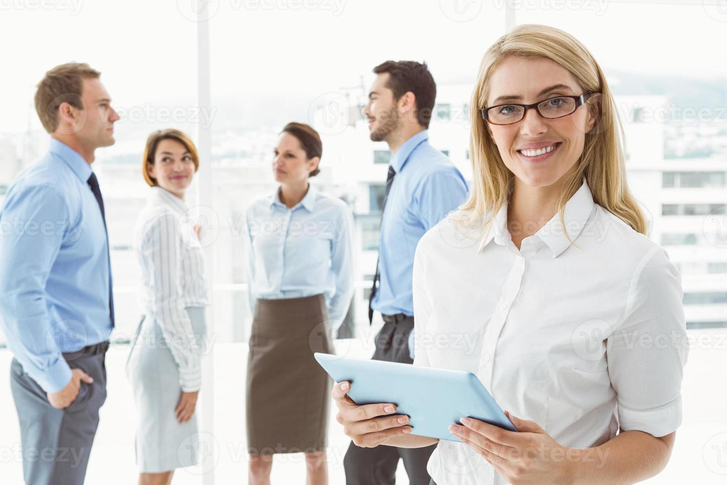 Geschäftsfrau mit digitalem Tablet mit Kollegen dahinter foto