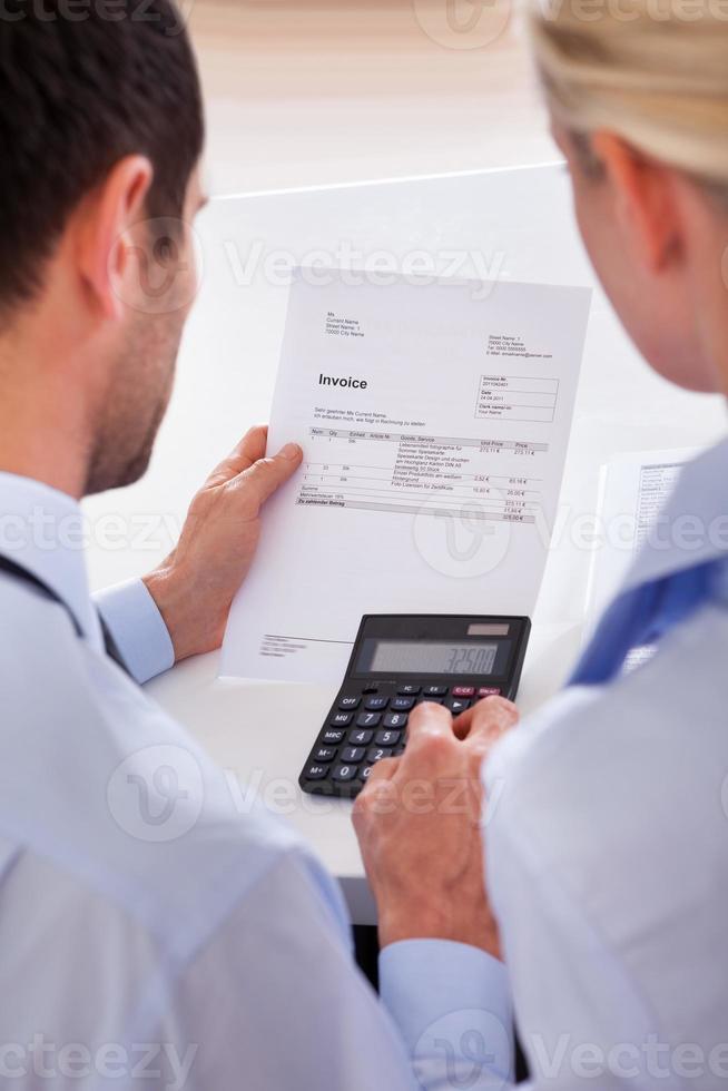 Kollegen, die eine Rechnung auf einem Taschenrechner prüfen foto