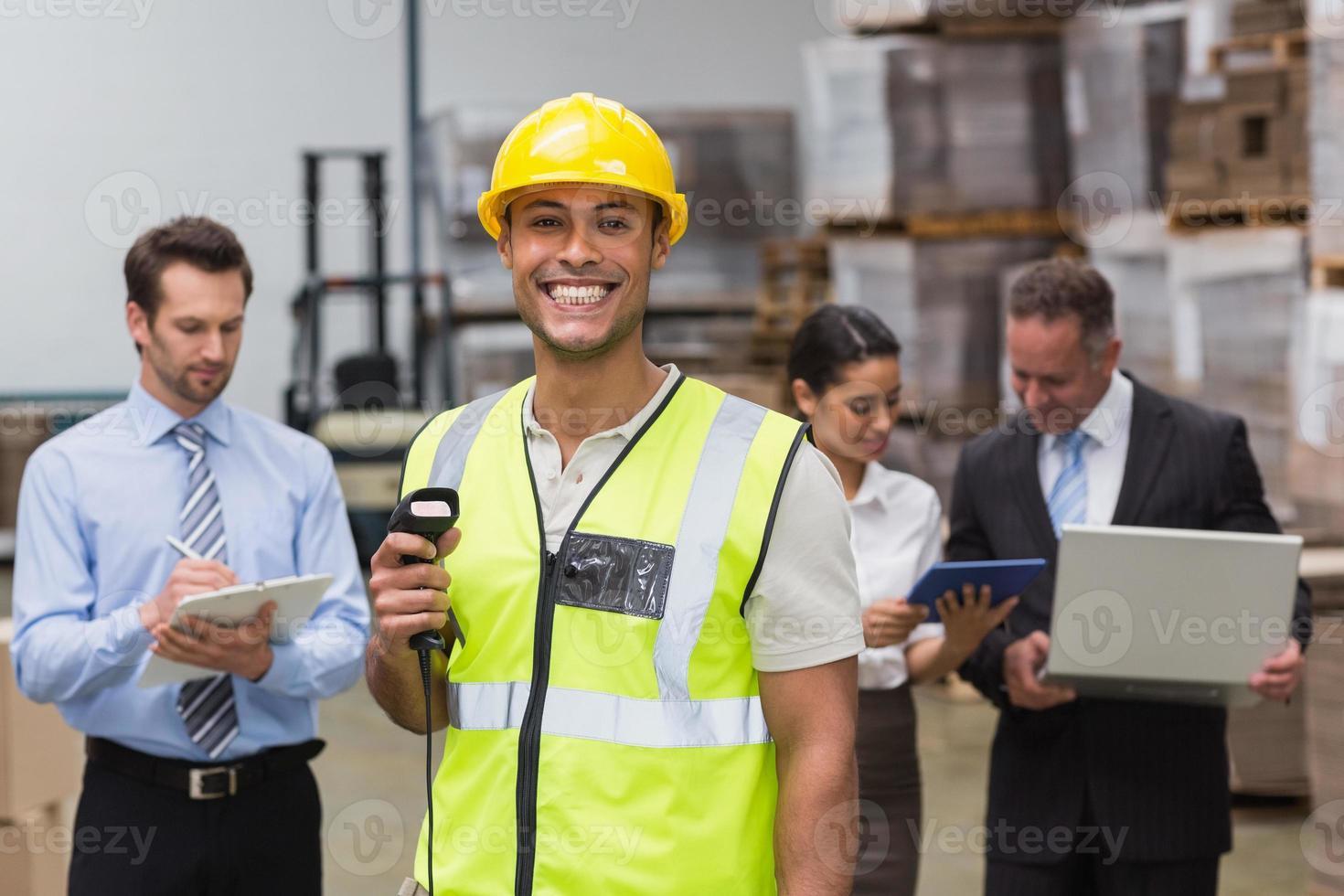 Arbeiter steht mit Scanner vor seinen Kollegen foto