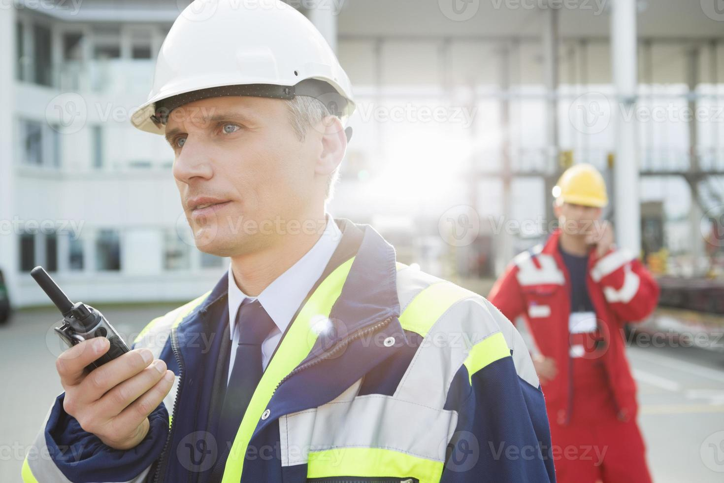 männlicher Arbeiter mit Walkie-Talkie mit Kollegen im Hintergrund foto