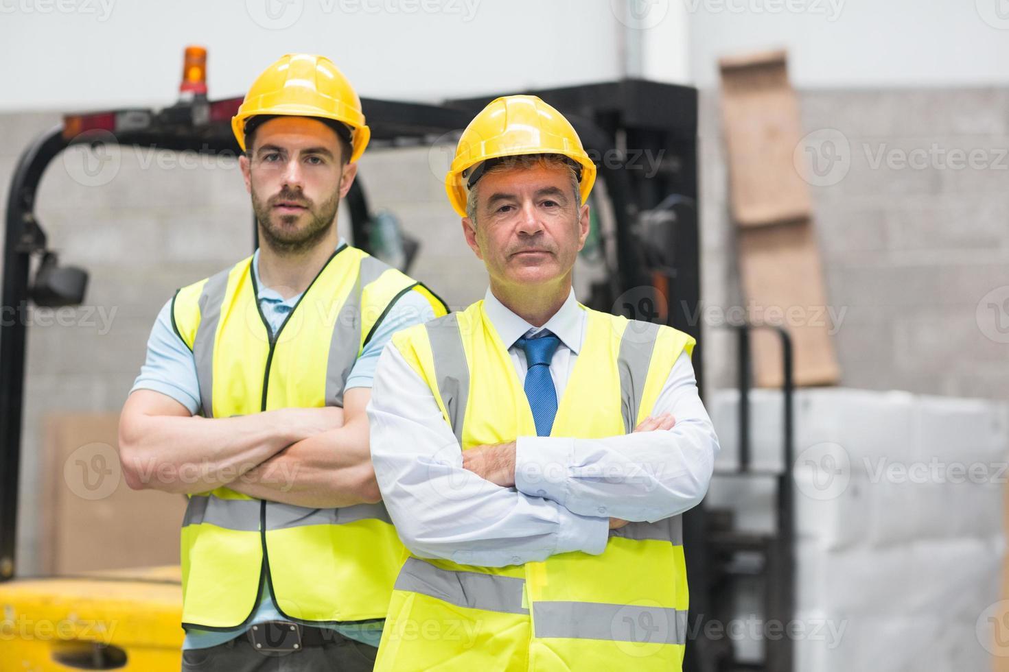 Manager mit verschränkten Armen und sein Kollege hinter ihm foto