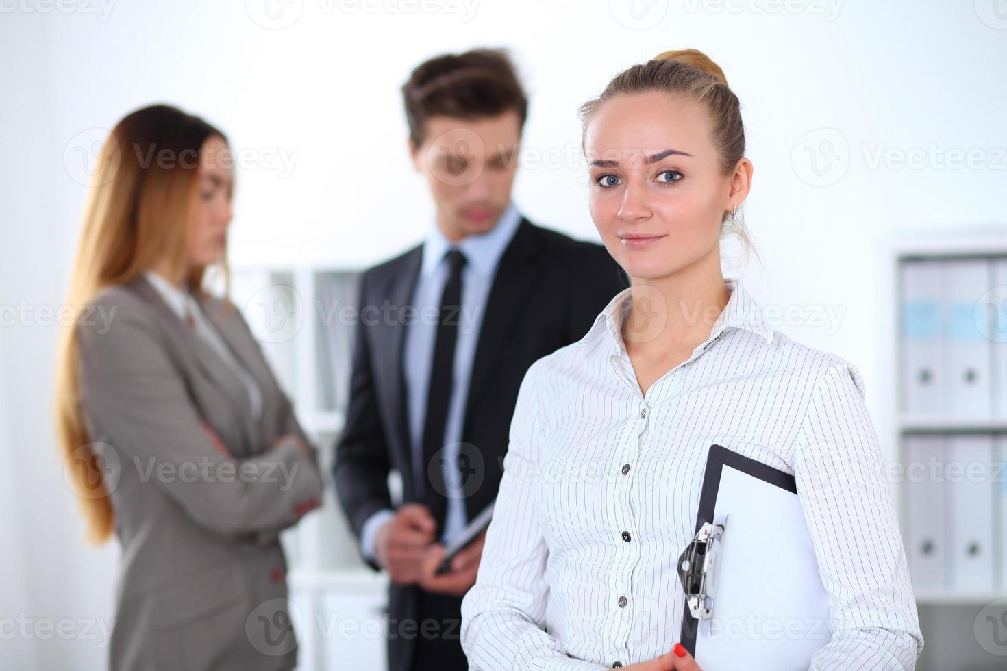 hübsche Geschäftsfrau im Büro mit Kollegen im Hintergrund foto