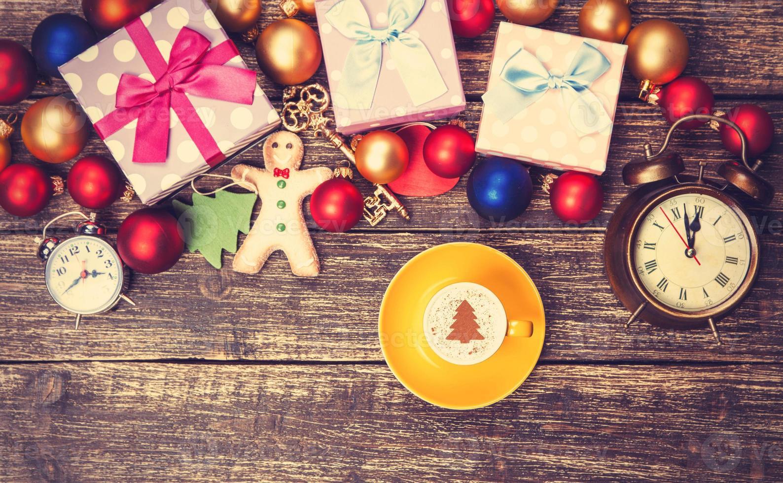 Frau, die Tasse Kaffee nahe Weihnachtsgeschenken hält foto