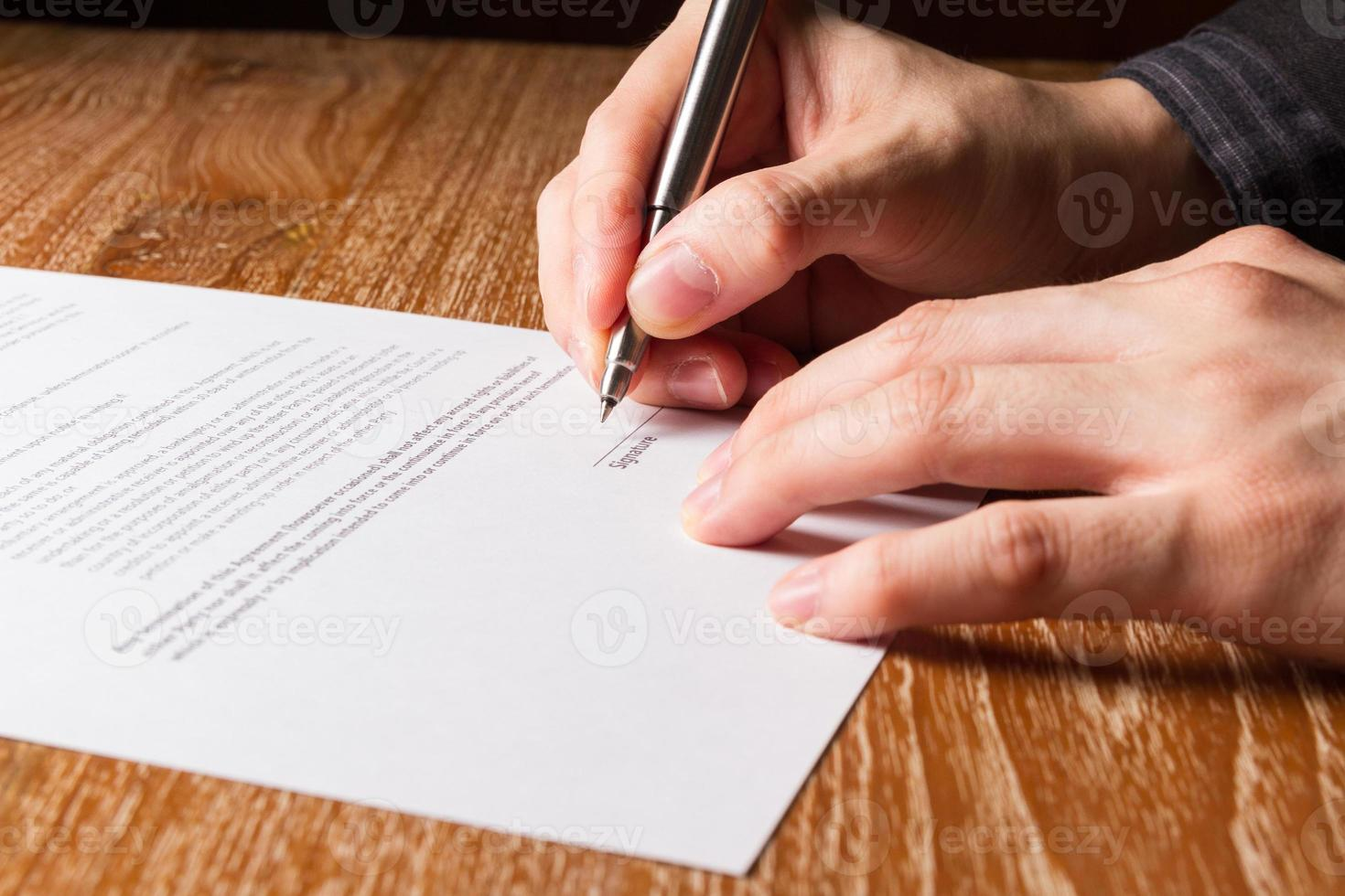 Geschäftsmann, der Vertrag unterzeichnet foto