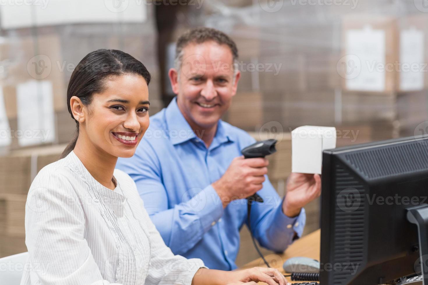 Manager-Scan-Box, während sein Kollege auf dem Laptop tippt foto